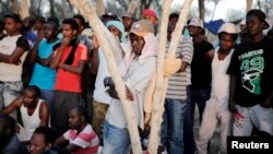 African asylum seekers gather in the shade of trees during a protest after leaving Holot open detention center in southern Israel's Negev desert, June 28, 2014.