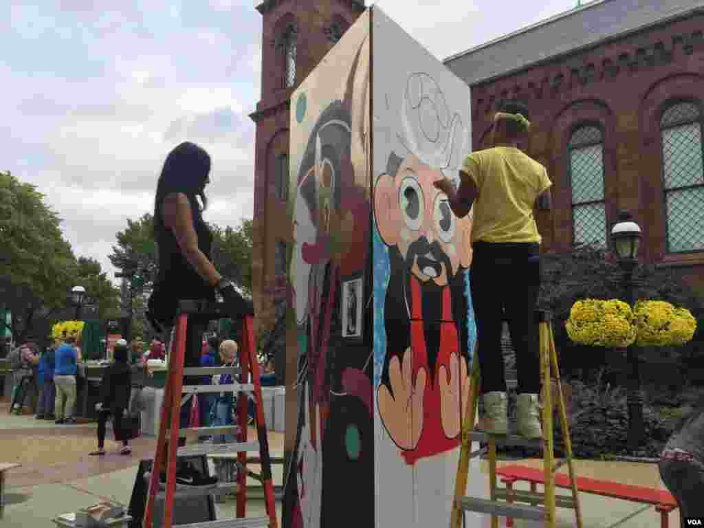 "Artsits Sita Sadeli (left) and ""Superwaxx"" stand on ladders for live mural painting. (Y. Jung/VOA)"