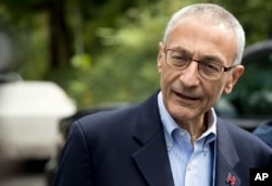 FILE - Hillary Clinton campaign chairman John Podesta speaks to members of the media outside Clinton's home in Washington, Oct. 5, 2016.