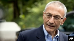 FILE - Hillary Clinton campaign chairman John Podesta speaks to members of the media outside Clinton's home in Washington. Pizzagate centers on emails that were stolen and made public by WikiLeaks in which Clinton campaign manager John Podesta and others discuss pizza. According to the theory, talk of pizza is code for pedophilia.