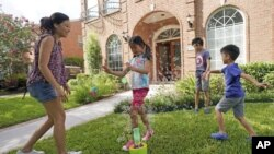 Vicky Li Yip sets up a bubble machine for her children, L to R, Kelsey, 8, Toby, 10 and Jesse, 5, outside their home, July 10, 2020 in Houston. She works from home and says online schooling has been exhausting, even with her husband helping out. (AP Photo/David J. Phillip)