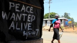 A woman walks past a message of peace in Kibera slum in the capital Nairobi, February 28, 2013.