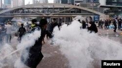 Demonstran melemparkan kaleng gas air mata pada aksi protes RUU Ekstradisi massal di Hong Kong, Rabu (12/6).
