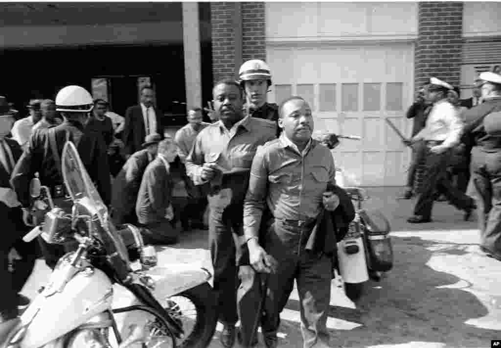 Rev. Ralph Abernathy and Martin Luther King, Jr., are taken by a policeman as they led a line of demonstrators into the business section of Birmingham, Alabama, April 12, 1963.