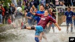 Pertandingan sepak bola tradisional tahunan di Sungai Windrush, desa Cotswolds di Bourton-in-the-Water, Inggris, Senin, 30 Agustus 2021. (Ben Birchall/PA via AP)