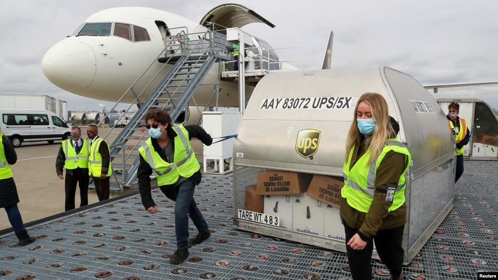 2020年12月13日UPS员工在肯塔基州路易斯维尔穆罕默德·阿里国际机场移动装载辉瑞疫苗的集装箱。(photo:VOA)