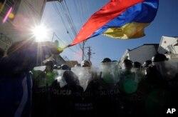 Un manifestante ondea la bandera de Ecuador durante protestas contra cambios constitucionales. Dic. 3 de 2015.