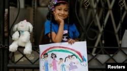 Jemima Christa-Faelist Tanamal (6 tahun) memperlihatkan gambar yang dibuatnya selama berdiam di rumah di tengah wabah virus corona (Covid-19) di rumah kakek-neneknya di Bekasi, 21 April 2020. (Foto: Reuters)
