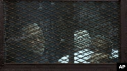 FILE - Members of Egypt's now banned Muslim Brotherhood are seen in detention in Cairo, Feb. 28, 2015.