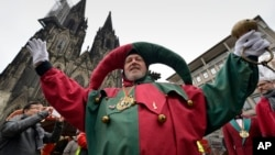 A reveler celebrates in front of the cathedral during the start of the Women's Street Carnival in Cologne, Germany, Feb. 4, 2016.