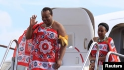 King of Swaziland Mswati III (Front) and one of his 13 wives disembark from a plane after arriving at Katunayake International airport in Colombo, Sri Lanka, August 13, 2012.