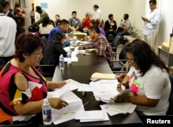 FILE - People fill out paperwork for the Deferred Action for Childhood Arrivals program at the Coalition for Humane Immigrant Rights of Los Angeles in Los Angeles, California, August 15, 2012.