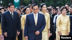 FILE - Thailand's Prime Minister Prayuth Chan-ocha (C), his wife Naraporn Chan-ocha (2nd R) and his cabinet pray for the health of Thailand's revered King Bhumibol Adulyadej, at the Siriraj hospital in Bangkok.