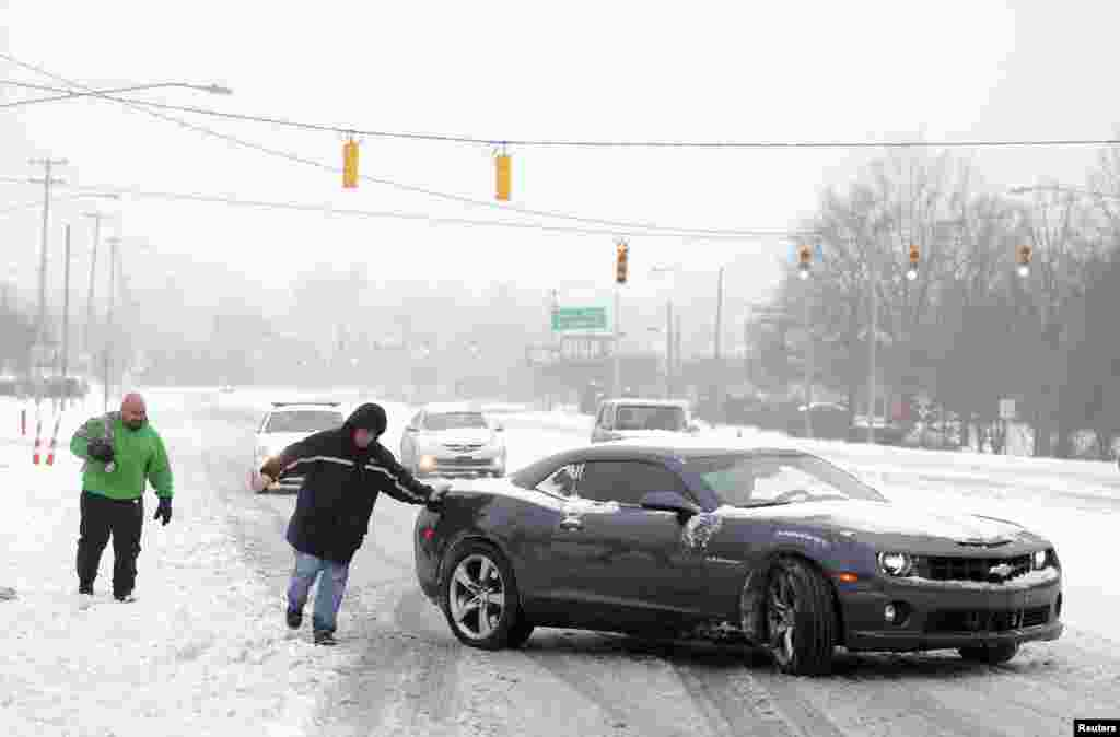 Tom Bladel works to push a stranded motorist back onto the road in Pineville, North Carolina, Feb. 12, 2014.