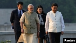 China's President Xi Jinping (R) walks with India's Prime Minister Narendra Modi (2nd L) during his visit to the Sabarmati river front in the western Indian city of Ahmedabad September 17, 2014. Xi arrived in India as the two Asian giants take steps to bo