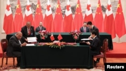 FILE - King Tupou VI of Tonga and Chinese President Xi Jinping attend a signing ceremonyat The Great Hall Of The People, in Beijing, China, March 1, 2018.