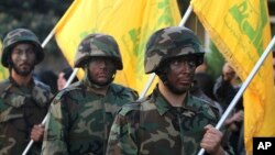FILE - Hezbollah fighters hold their group's flags at a rally in Nabatiyeh, southern Lebanon, Nov. 7, 2014.