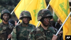 FILE - Hezbollah fighters hold their group's flags at a rally in Nabatiyeh, southern Lebanon.