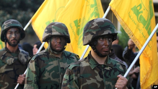 FILE - Hezbollah fighters hold their group's flags at a rally in Nabatiyeh, southern Lebanon, Nov. 7, 2014.  The Gulf Cooperation Council announced Wednesday it has labeled the Lebanese militant group a terrorist organization.
