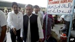Pakistan's Railway Minister Haji Ghulam Ahmad Bilour, center, arrives at the Attari railway station on the Samjhauta Express train near Amritsar, India, May 19, 2011.