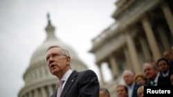 FILE - U.S. Senate Majority Leader Harry Reid, with other Democratic Party Senate members in the background, is seen on the steps of the U.S. Capitol in Washington, D.C..