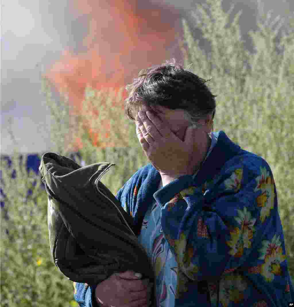 A woman cries near her burning house after shelling by government forces in the city of Slovyansk, Donetsk Region, eastern Ukraine.