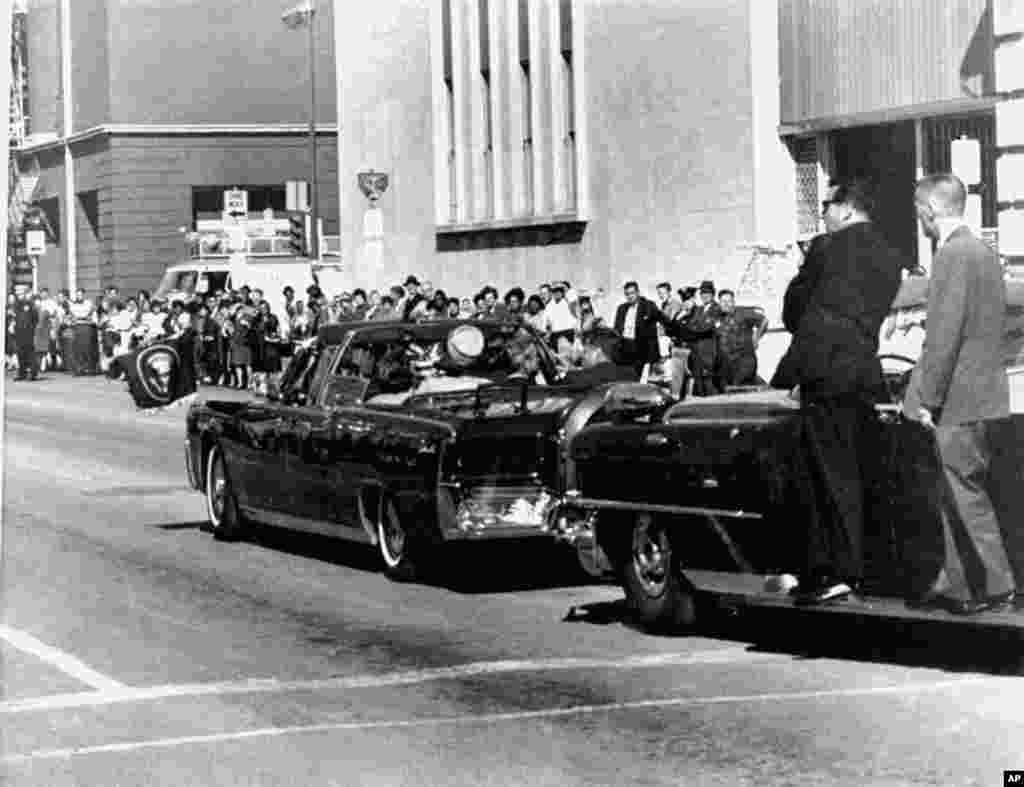 The presidential limousine carrying President John F. Kennedy and first lady Jacqueline Kennedy is followed by secret servicemen on running boards, Dallas, Texas, Nov. 22, 1963.