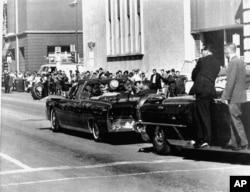 FILE - The presidential limousine carrying President John F. Kennedy and first lady Jacqueline Kennedy is followed by secret servicemen on running boards, Dallas, Texas, Nov. 22, 1963.