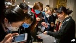 Nhà báo Trung Quốc đeo khẩu trang xem một thông cáo báo chí của chính quyền trước một cuộc họp báo tại Bắc Kinh.