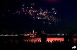 Kembang api menghiasi angkasa di sekitar Pelabuhan New York dan Patung Liberty saat New York dan kota-kota lain di sekitar negara bagian New York mengakui tingkat vaksinasi COVID-19 di New York telah mencapai 70 persen, Selasa, 15 Juni 2021.
