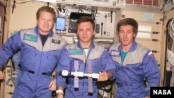 Expedition 1, the first space station crew, poses inside the Zvezda service module with a model of the young International Space Station. Pictured in December 2000 (from left) are Commander William Shepherd and Engineers Yuri Gidzenko and Sergei Krikalev.