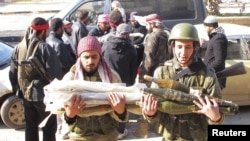 Free Syrian Army fighters transport ammunition which was seized from government forces' Wadi al-Daif military base at Maaret al-Numan, in the Idlib governorate in the northwest of Syria, December 29, 2012.