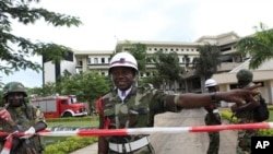 A Nigerian military policeman directs U.N. workers to another entrance, as he stands guard where a day earlier a suicide bomber crashed through an exit gate and detonated a car full of explosives in the reception area of U.N. headquarters, in Abuja, Augus