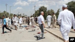 Iraqis gather at the scene of a bomb attack in Baqouba, northeast of Baghdad, Iraq, Friday, May 17, 2013. A bomb killed dozens of people at a Sunni mosque in central Iraq, hitting worshippers as they were emerging from Friday prayers, security officials s