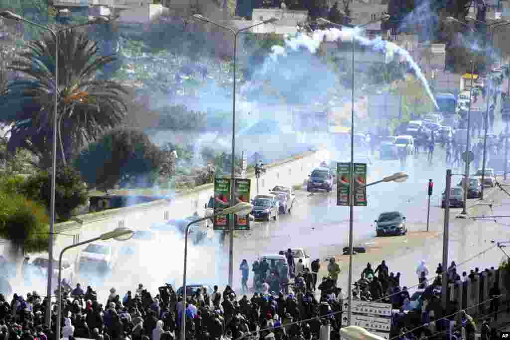 A tear gas canister flies in the air as thousands of Tunisians gathered at el Jallez cemetery to attend the funeral of slain opposition leader Chokri Belaid, Feb. 8, 2013.