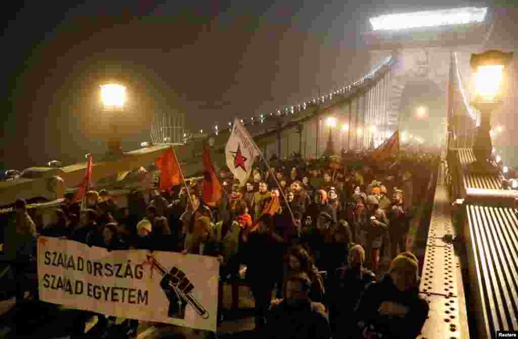 """Macaristan'ın başkenti Budapeşte'de yeni çalışma yasasını protesto edenler köprüde yürüyor. Göstericinin taşıdığı dövizin üzerinde """"Özgür Ülke, Özgür Üniversite"""" yazıyor"""