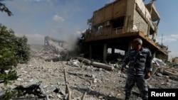 Seorang pejuang Suriah terlihat di Pusat Penelitian Sains di Damascus, Suriah, 14 April 2018.