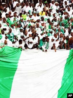 "Nigerian soccer supporters unfurl a massive national flag during a 2009 World Cup qualifier in Lagos...Super Eagles fans are expected to ""go crazy"" during the World Cup in South Africa"
