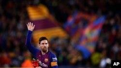 Penyerang Barcelona Lionel Messi melambai ke arah penonton saat ia memegang trofi pemain terbaik La Liga Spanyol sebelum pertandingan sepak bola antara FC Barcelona dan Atletico Madrid. (Foto: AP)