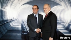 Swiss Federal President Johann Schneider-Ammann, right, speaks with French President Francois Hollande, left, on the opening day of the Gotthard rail tunnel, the longest tunnel in the world, at the fairground Rynaecht at the northern portal in Erstfeld, S