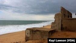 Un homme marche à côté des vagues sur la côte du village d'Afidégnigba au Togo, 19 septembre 2018. (VOA/Kayi Lawson)