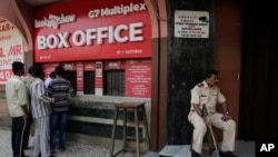 "A policeman guards as people buy tickets at a movie theatre screening Bollywood film ""Padmaavat"" in Mumbai, India, Jan. 25, 2018."