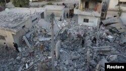 Người dân kiểm tra hiện trường bị tàn phá từ cuộc không kích được thực hiện bởi các lực lượng không quân Nga tại thành phố Nawa, Deraa, Syria, ngày 21/11/2015.