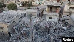 Warga memeriksa lokasi yang rusak parah akibat serangan udara Rusia di kota Nawa, Deera, Suriah (21/11).