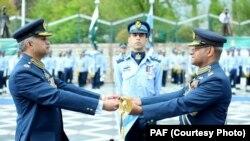 سبدوش ہونے والے ایئر چیف سہیل امان نئے ایئر چیف مجاہد انور خان کو علامتی شمشیر سونپ رہے ہیں