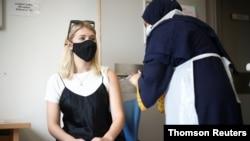 Seorang perempuan menerima suntikan vaksin COVID-19 di rumah sakit Central Middlesex di London, Inggris (foto: dok).