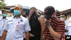 Polisi mengawal Collum Park (kanan), dan Aaron Wayne Coyle (kedua dari kanan), menuju mobil polisi di markas polisi daerah di Denpasar, Kamis, 3 September 2020.