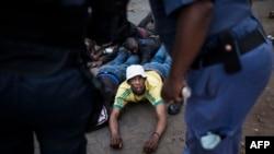 Un homme est arrêté par des membres de la police métropolitaine d'Ekurhuleni dans le canton de Johannesburg Katlehong, le 5 septembre 2019.