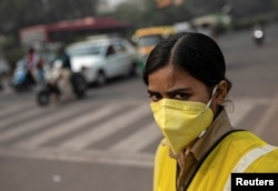 FILE - A policewoman wears a mask to protect herself from air pollution in New Delhi, India, Nov. 4, 2019.