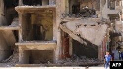 시리아 휴전 이틀째인 13일 북동부 도시 카미실리에서 장난감총을 든 소년이 내전으로 파괴된 건물 앞을 지나고 있다.